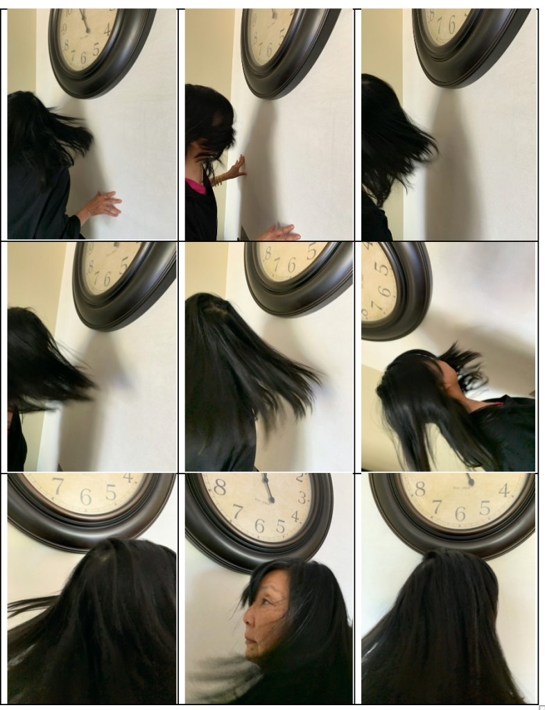 photo of woman whipping her hair. part of a clock visible in background.